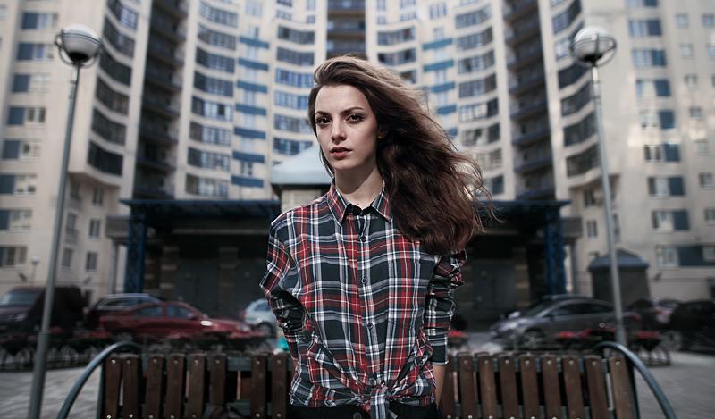 Девушка на фоне многоэтажного дома. Фото Ефима Шевченко