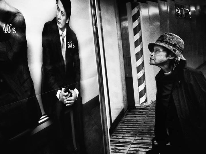 Бабушка возле рекламного плаката. Фото: Tatsuo Suzuki