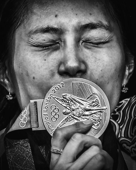 Кореянка Ким Джи Ён целует свою золотую медаль во время церемонии награждения победителей в женских соревнованиях по индивидуальной сабле. Фотография получила второй приз в категории «Спорт» на 56-ом профессиональном конкурсе фотожурналистики World Press Photo
