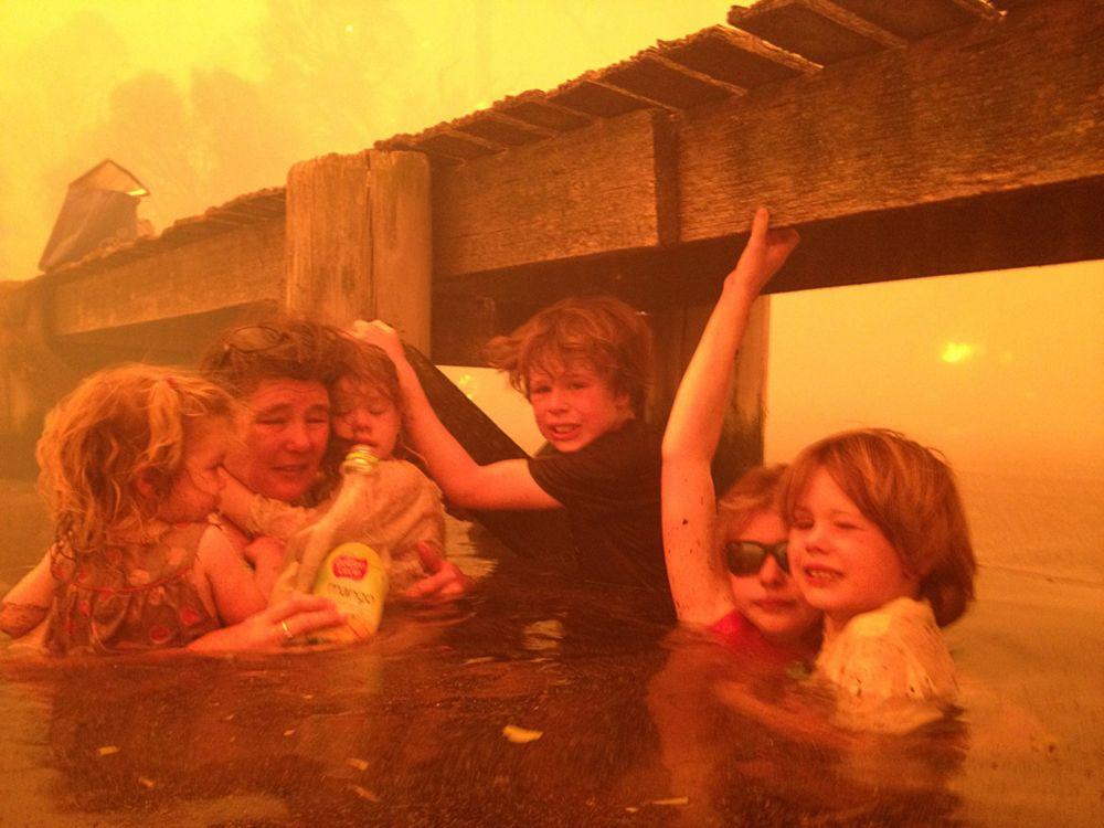 Тэмми Холмс и ее внуки укрываются под причалом во время лесного пожара в Австралии. Фото: Tim Holmes—AP