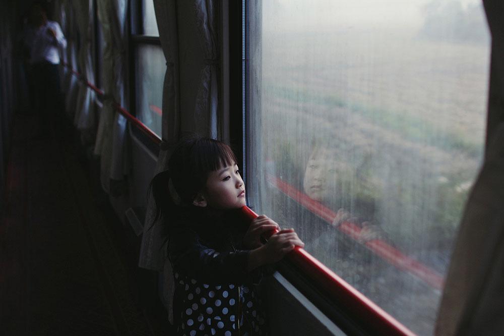 Девочка смотрит в окно 24-часового поезда на проплывающий мимо пейзаж. Место съёмки: Китай. Номинация: Youth, Portraits, 1 место. (Paulina Metzscher/2014 Sony World Photography Awards)
