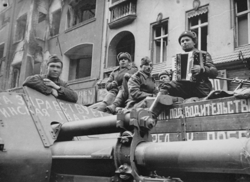 Советские артиллеристы слушают игру на аккордеоне своего товарища на улице Берлина. На переднем плане — 122-мм гаубица М-30. Источник: altyn73.livejournal.com. Май 1945 года. Автор неизвестен