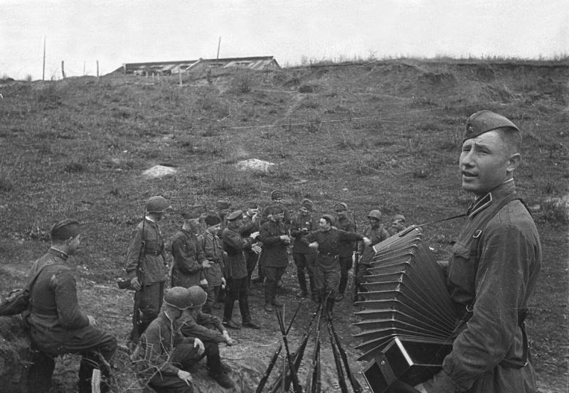 Советский солдат-гармонист и отдыхающие бойцы РККА. Октябрь 1942 года.  Автор: Наталья Боде