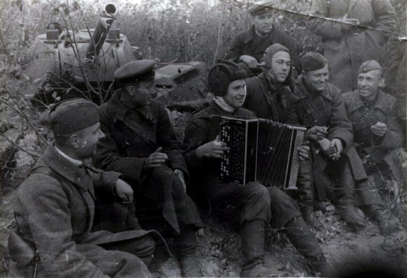 Советские солдаты и командиры слушают играющего на баяне танкиста. Позади танк Т-34 в окопе. 1941 год. Автор неизвестен
