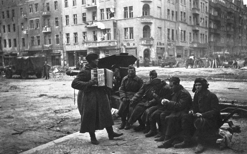 Советские солдаты слушают гармониста, сидя на станине 122-мм гаубицы М-30 на улице Берлина. 1945 год. Автор фото:  Аркадий Шайхет