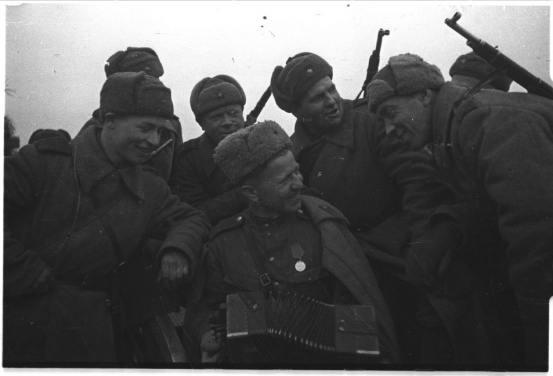 """Советские солдаты слушают выступление своего товарища играющего на гармони. Авторское название фото - """"Отдых после боя"""".  1943 год. Автор: Наталья Боде"""