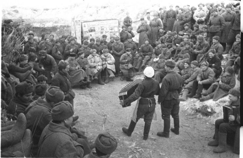 Советские солдаты и офицеры слушают выступление гармониста в перерыве между боями под Сталинградом. 1943 год . Наталья Боде