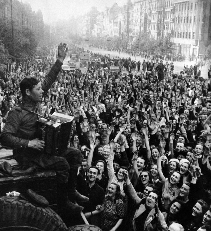 Советский солдат с гармонью и ликующие жители Праги.  Прага, Чехословакия. 09 мая 1945 года. Автор: Анатолий Егоров