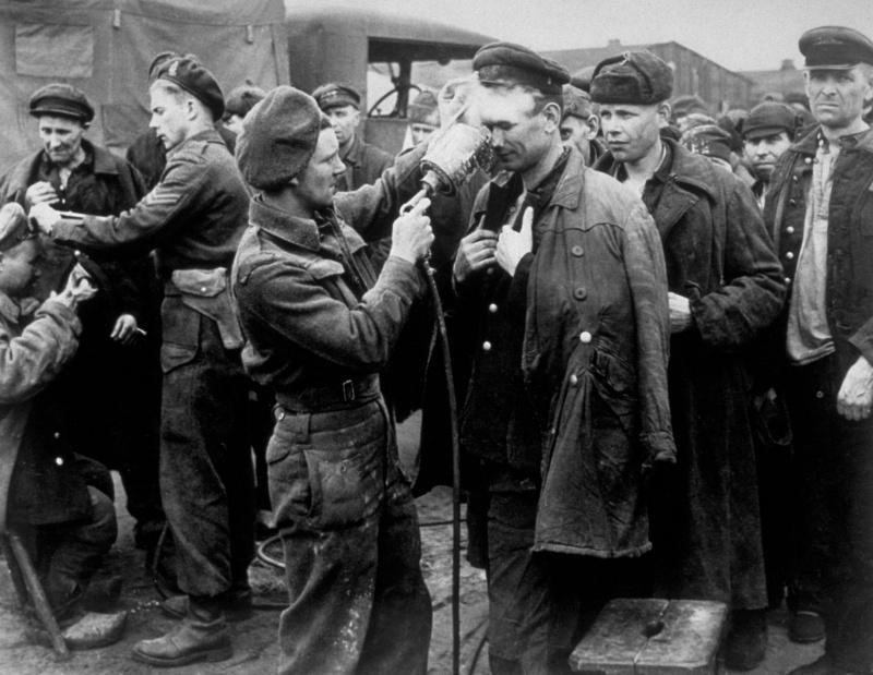 Канадские военные проводят дезинфекцию освобожденных советских военнопленных в городе Фризойте (Friesoythe), Германия. Апрель 1945