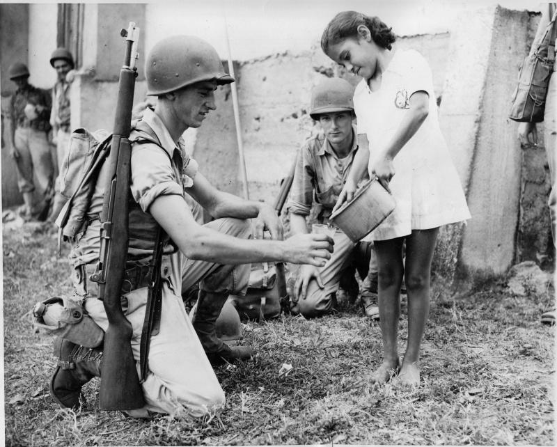 Панамская девочка дает напиться воды американскому солдату во время учений армии США в Панаме в 1942 году.