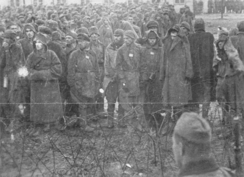 Советские военнопленные у колючей проволоки концентрационного лагеря «Шталаг XVIIIA» (Stalag XVIIIA).  Фотография сделана пленным британским капралом Эриком Эвансом (Eric Evants), находившимся в том же лагере. Вольфсберг, Австрия. Автор: Эрик Эванс