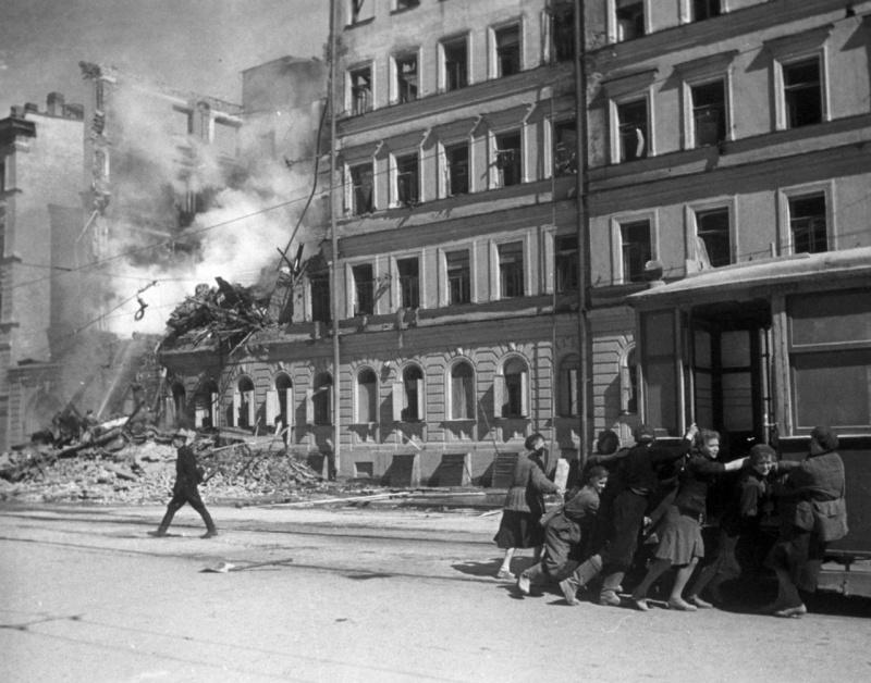 Жители блокадного Ленинграда передвигают трамвайный вагон подальше от фасада разрушенного бомбардировкой дома.  1942