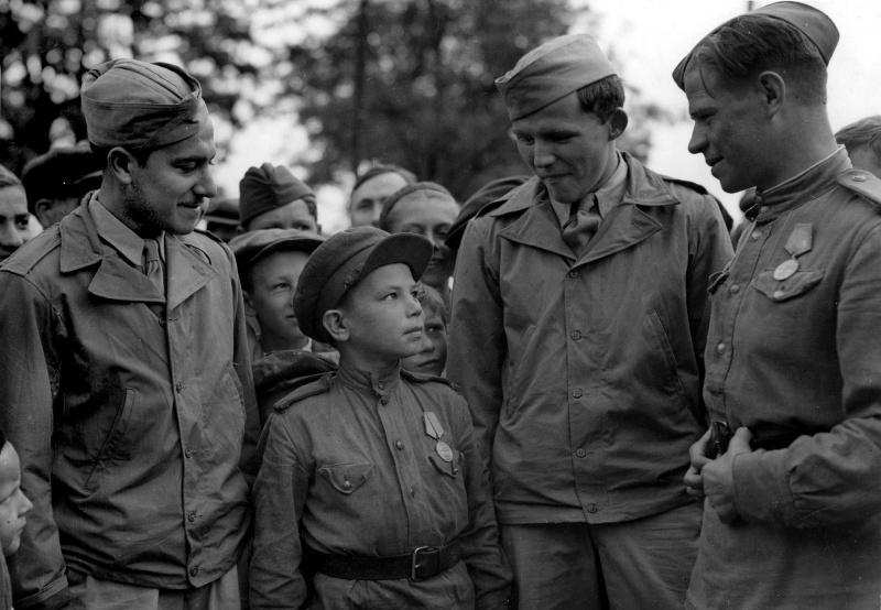 Сержант С. Вайншенкер и техник-сержант Вильям Топпс с сыном полка 169 авиабазы особого назначения. Имя неизвестно, возраст — 10 лет, служил помощником техника по вооружению. Аэродром Полтава.