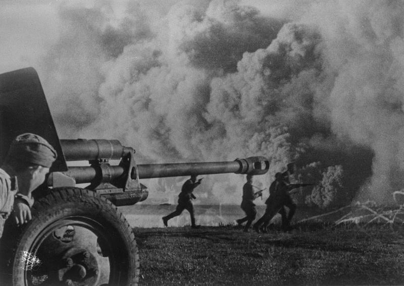Советский артиллерист наблюдает за атакой пехоты у 76-мм дивизионной пушки ЗиС-3. Яков Рюмкин