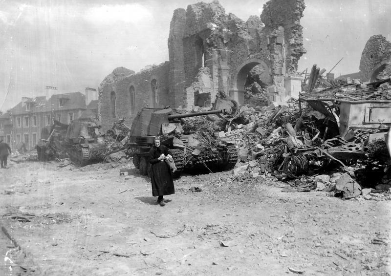 Пожилая женщина идёт мимо разрушенной церкви города Ронсе. У подножия церкви уничтоженная колонна немецкой техники, в том числе две САУ Marder III.