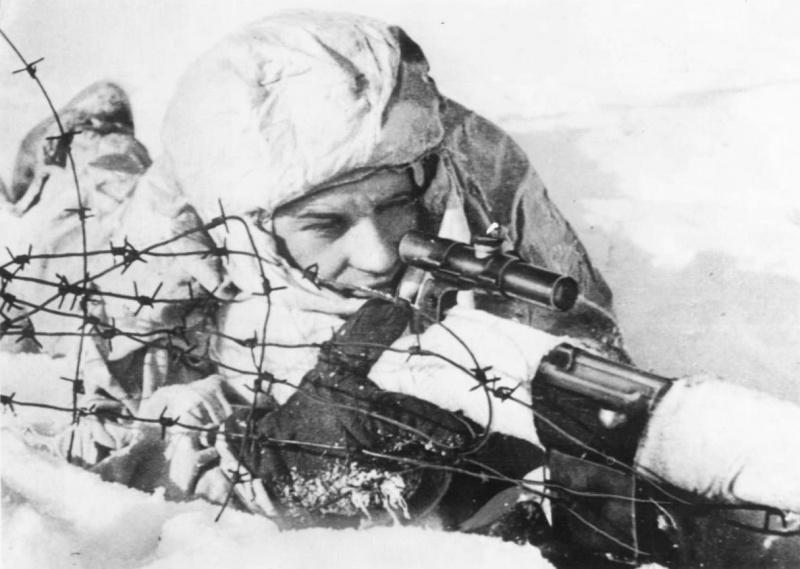 Советский снайпер сержант Жидков, вооруженный самозарядной винтовкой СВТ-40 с оптическим прицелом ПУ, на огневой позиции. Северный фронт.