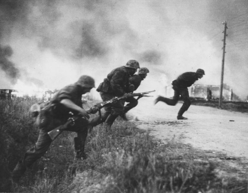 Солдаты дивизии СС «Рейх» перебегают дорогу на фоне горящей советской деревни. 1941. Источник: www.nationaalarchief.nl.