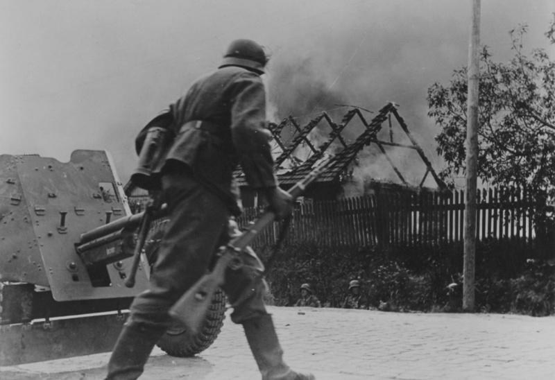 Немецкий солдат переходит улицу горящей советской деревни у 37-мм противотанковой пушки PaK 35/36. Фотография опубликована на обложке американского журнала Newsweek от 20 октября 1941 года.  Источник: www.nationaalarchief.nl.