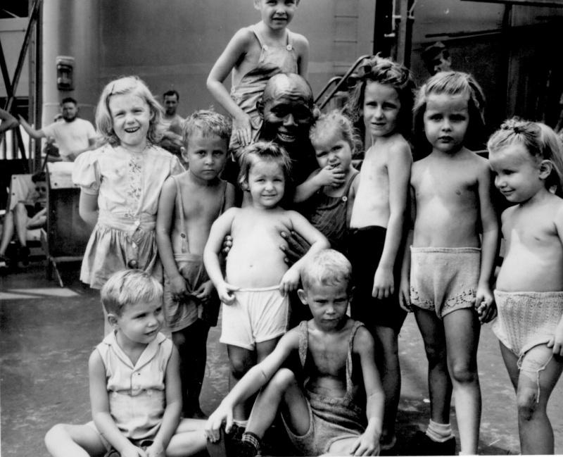 Американские дети из филипинского лагеря интернированных на борту транспорта Джеан Лафитт (SS Jean Lafitte), на пути в США в компании чернокожего повара Пендлтона «Бамблби» Томсона (Pendleton «Bumblebee» Thompson). Томсон добровольно исполнял обязанности повара в лагере, где дети были интернированы. Источник: Национальный архив США.