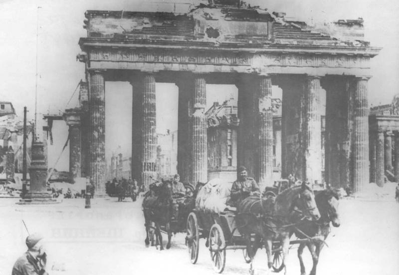 Советские солдаты на конных подводах проезжают возле Бранденбургских ворот в Берлине. 1945. Авторы: Борис Шейнин