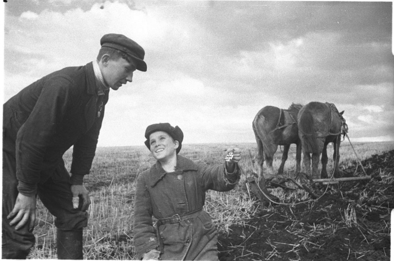 Советский мальчик в освобожденной деревне показывает товарищу найденный при полевых работах немецкий Железный Крест. Юго-Западный фронт. Июнь-июль 1942. Автор: Наталья Боде