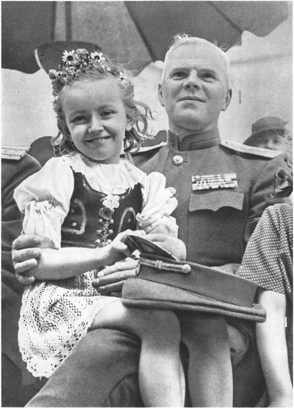Чешская девочка сидит на коленях у генерала-лейтенанта Красной Армии во время праздника в Праге.