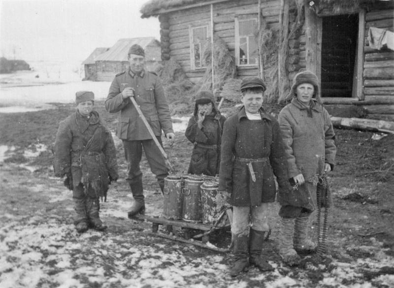 Немецкий солдат с детьми в оккупированной советской деревне. Два самых маленьких мальчика курят папиросы.