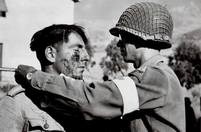 Медик из состава 48-го медицинского батальона 2-й бронетанковой дивизии армии США делает перевязку раненому немецкому солдату. Июль 1943.