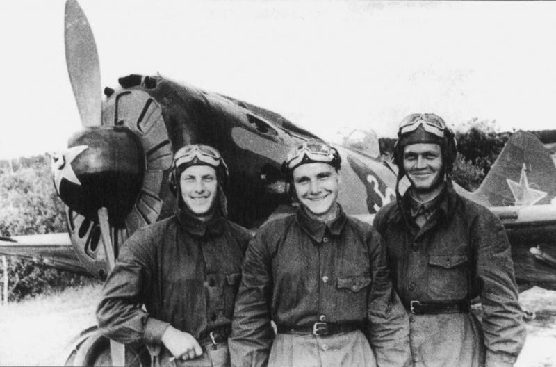 Советские летчики-сержанты С. Слесарчук, С. Гозин и А. Перевера из 34-го истребительного авиаполка ПВО Москвы у истребителя И-16. Истребитель И-16 оснащен направляющими для реактивных снарядов РС-82. На борту машины надпись «За Родину». 1942 год.