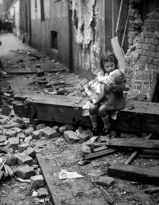 Английская девочка с куклой на обломках своего дома, разрушенного немецкой бомбардировкой.