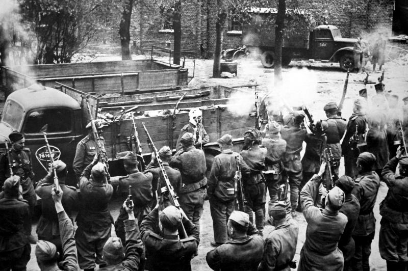 Советские бойцы дают прощальный залп в честь погибших танкистов.