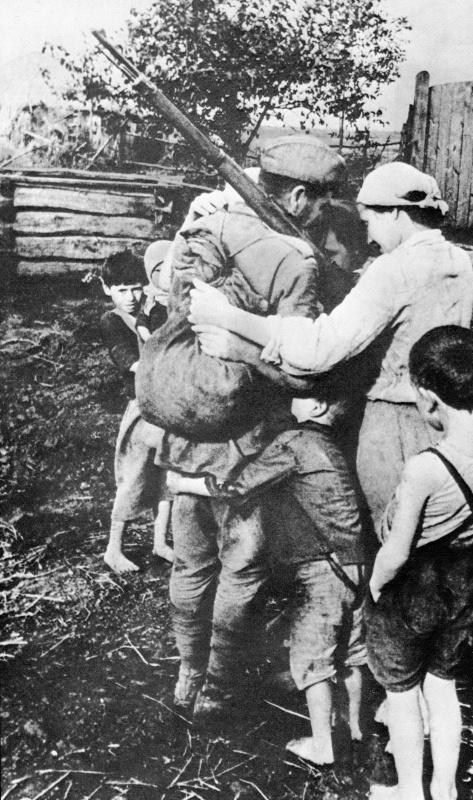 Советский солдат обнимает свою семью после долгого расставания. Авторское название фото: «Мимо родного села». 1943 год. Автор: Олег Кнорринг