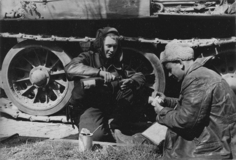 Советские танкисты обедают у своего танка Т-34.