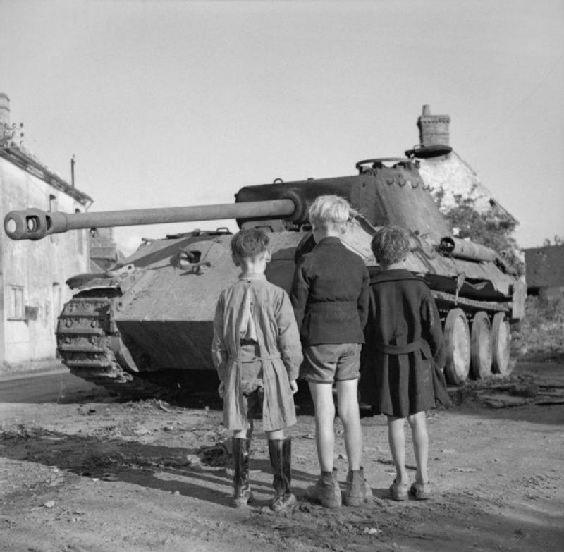 Французские дети смотрят на подбитый немецкий танк Pz.Kpfw. V «Пантера», уничтоженный в Фалезском котле. Нормандия, Франция. 15.08.1944