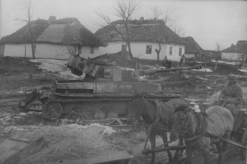 Советский солдат на конной подводе проезжает возле подбитого немецкого среднего танка Pz.Kpfw. IV в украинской деревне. На танке пометка советской трофейной команды: «УА 434». 1944