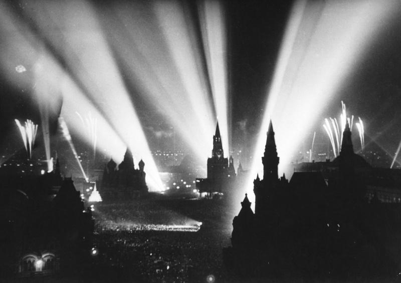 Салют Победы в Москве. Вид на Красную площадь. Праздничный салют начался 9 мая 1945 года в 22.00. Последовало тридцать залпов из тысячи орудий в небо, освещаемое прожекторами.