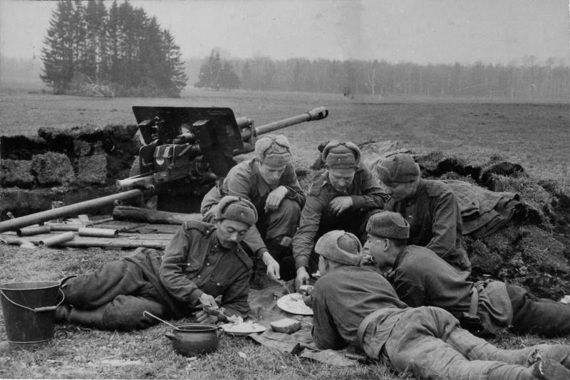 Советские артиллеристы обедают рядом с орудием на подступах к Берлину.  Апрель 1945.