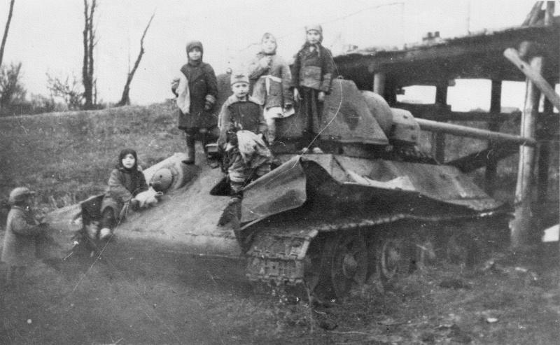 """Дети на брошенном у моста советском танке Т-34-76. Фото не ранее осени 1942 года, так как танк оснащен башней-""""гайкой"""", которую стали ставить с этого времени."""