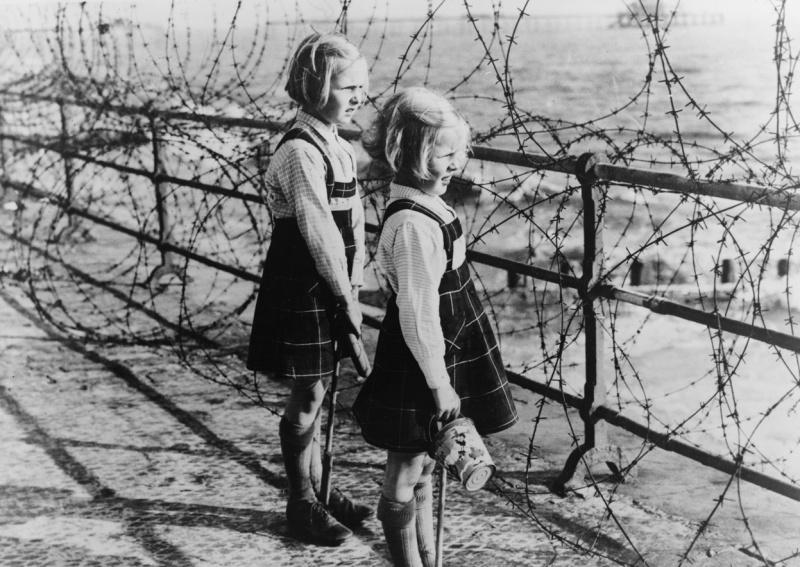 Две девочки смотрят сквозь колючую проволоку береговых укреплений на море и пляж на южном побережье Англии во время битвы за Британию.