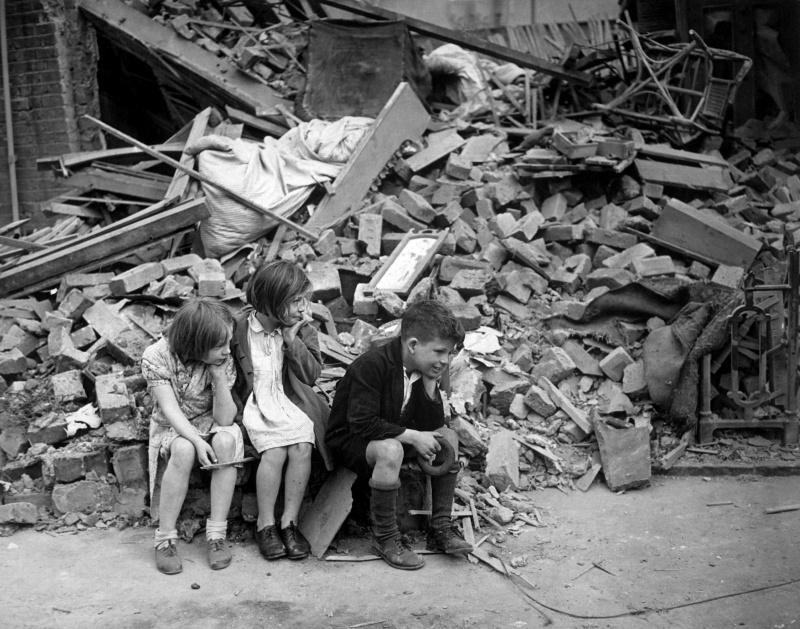 Дети восточного пригорода Лондона у разрушенного здания, сентябрь 1940 года.