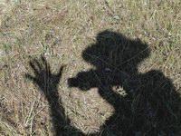 2. «Автопортрет»  Высокое полуденное солнце отбросило тень на поверхность скошенного луга. В этот день я испытывал возможности только что купленного цифровика с поворотным экранчиком видоискателя. Он оказался очень удобен для охоты за собственной тенью. В результате получился снимок о летнем солнечном дне, о запахе сена, о фотографе, который обещает внуку показать птичку. А на фотобумаге, по сути дела, только черная тень и однородный фон из травинок.  Камера Nikon Сoolpix 5000. Чувствительность 100 ASA. Выдержка 1/100 сек. Диафрагма 8.