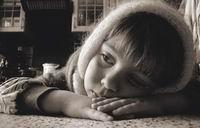 7. «Гномик заболел»  Больной внук сидел за кухонным столом в метре от окна и грустил. Я положил камеру прямо на стол в пятнадцати сантиметрах от его носа, надев на объектив широкоугольную насадку. Если бы камера была пленочной, то фокусное расстояние такого объектива было бы равно 19 мм. Снимать портреты шириком в упор – значит почти гарантированно гипертрофировать все выступающие над плоскостью лица части физиономии. Взрослый человек в данной ситуации выглядел бы карикатурно, а вот малышу низкая точка съемки не повредила. Мягкий боковой свет из окна отлично передал объемы головки, прорисовал нежную кожу ребенка и фактуру шерстяного платка. Лайтдиск (справа, в тридцати сантиметрах от границы кадра) слегка заполнил светом провальную тень. Глубина резкости широкоугольной оптики настолько велика, что фон оказался почти резким, но благодаря резким перспективным сходам, также присущим таким объективам, все предметы заднего плана уменьшились и не отвлекают внимания от главного в кадре – глаз ребенка.  Камера Nikon Сoolpix 5000. Чувствительность 100 ASA. Выдержка 1/30 сек. Диафрагма 5,6.